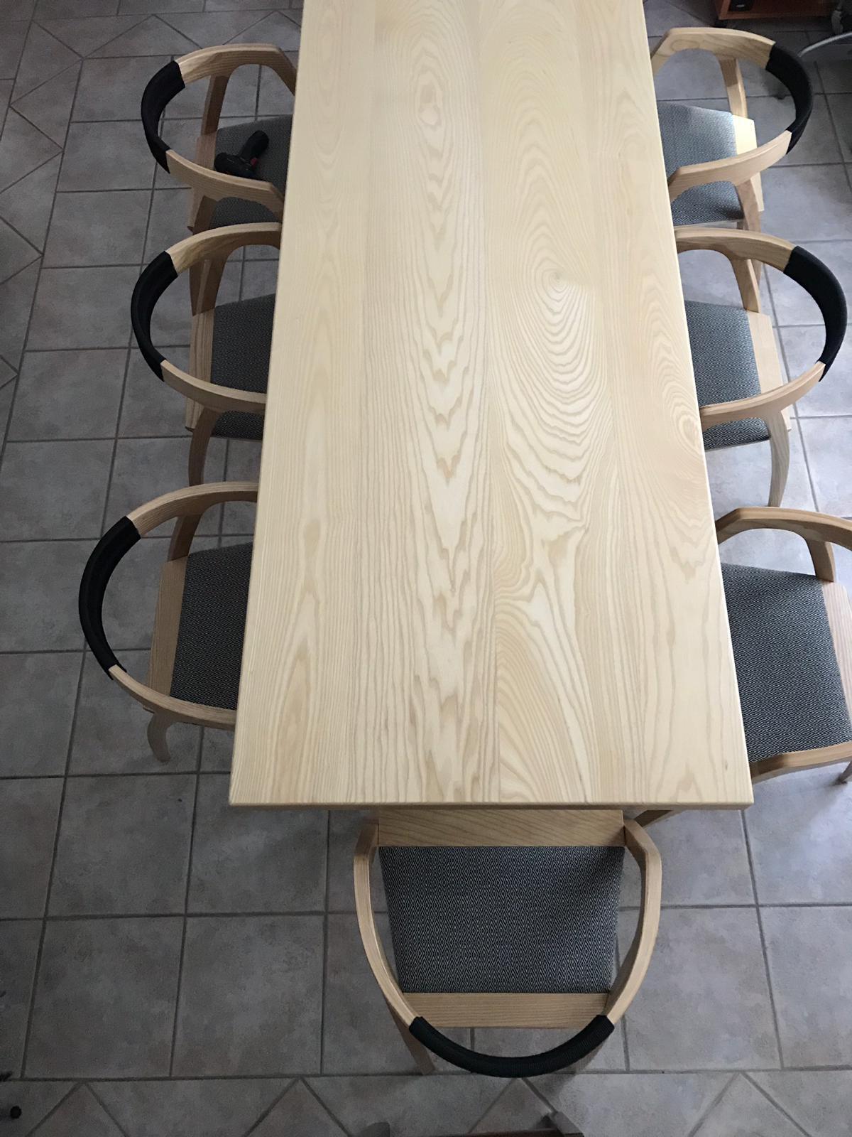 Tavolo in legno massello frassino verniciatura naturale e struttura in acciaio nero opaco. Sedie in frassino con fondelli in tessuto realizzati al telaio a mano